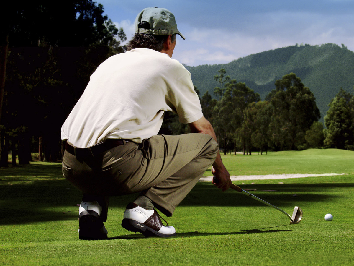 Golfer kneeling and planning shot with iron